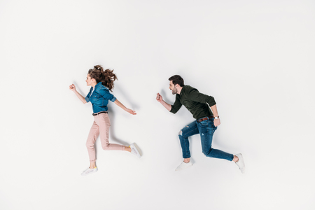top view of couple pretending to run isolated on white Archivio Fotografico