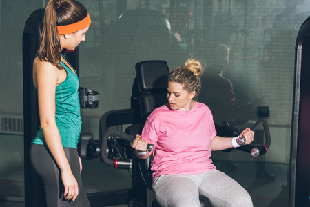 overweight woman working out on training apparatus while trainer watching her Stockfoto