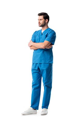 Knappe mannelijke verpleegster die blauw uniform draagt dat op wit wordt geïsoleerd Stockfoto