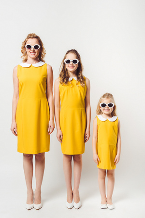 mother and daughters in similar retro style yellow dresses standing in row on white