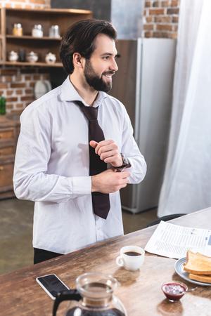 smiling handsome loner businessman buttoning sleeve at kitchen