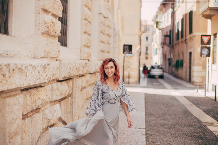 smiling elegant girl in glamorous grey dress walking in Verona Stock Photo