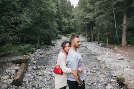 side view of happy young couple in love hugging near rapid mountain river in forest