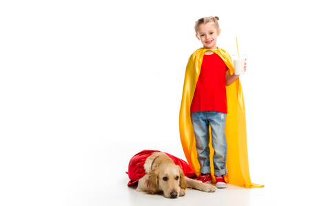 Happy supergirl holding milkshake with lying golden retriever in red cape isolated on white
