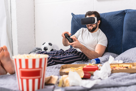 smiling loner using virtual reality headset and playing video game in bedroom Stock Photo