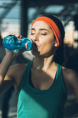 sporty woman drinking water at gym with closed eyes Stockfoto