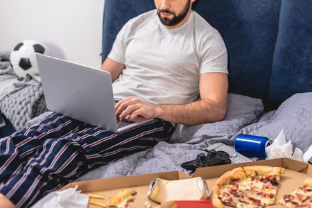 cropped image of loner using laptop in bedroom Stock Photo
