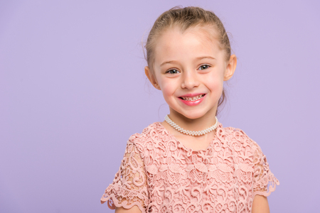 Pretty smiling child isolated on violet