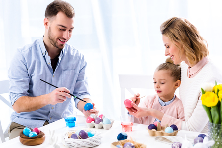 Family coloring Easter eggs with painting brushes Stock Photo