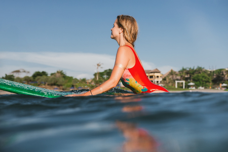 side view of young attractive woman in swimming suit resting on surfing board in ocean with coastline on background Stok Fotoğraf