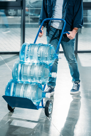 Delivery man pushing cart with water bottles
