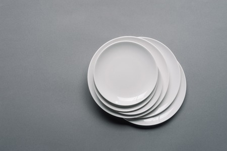 Stack of white porcelain plates on grey background 스톡 콘텐츠