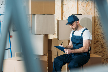 Delivery man filling cargo declaration while sitting by boxes
