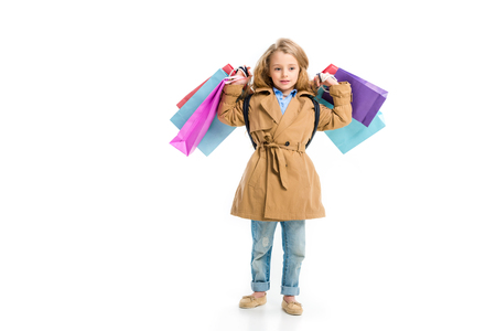 Kid in trench coat standing with different shopping bags in hands isolated on white
