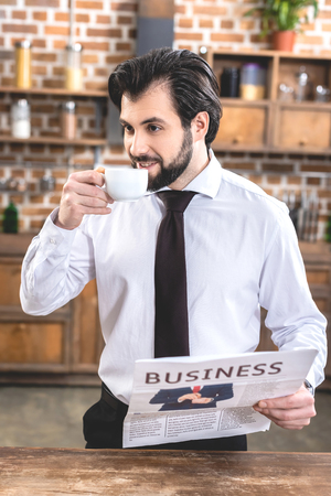 handsome loner businessman drinking coffee and holding newspaper at kitchen
