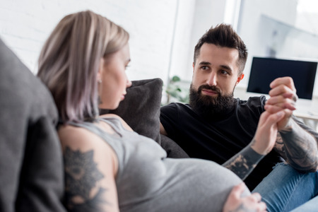 tattooed pregnant girlfriend and boyfriend holding hands at home
