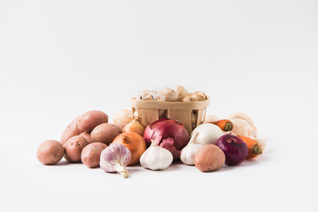 heap of mushrooms laying in basket over vegetables on white background Stock Photo