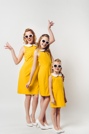happy mother and daughters in similar retro style yellow dresses on white 版權商用圖片
