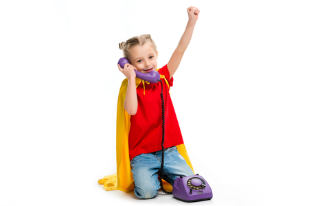 Smiling little supergirl gesturing and talking on phone isolated on white