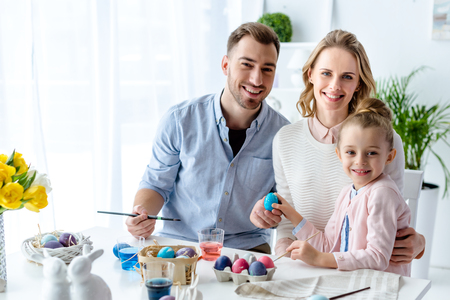 Smiling family with daughter coloring Easter eggs Standard-Bild - 111567352