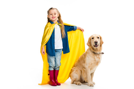 Supergirl in yellow cape standing with golden retriever  beside isolated on white Stock Photo