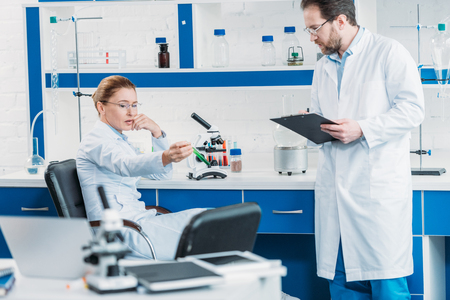 scientific researcher looking at flask with reagent in hand with colleague near by in laboratory