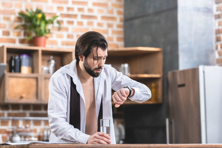 handsome loner businessman with hangover checking time at kitchen