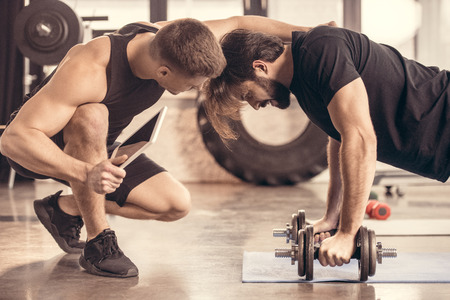 side view of muscular trainer pushing man doing push ups on dumbbells in gym