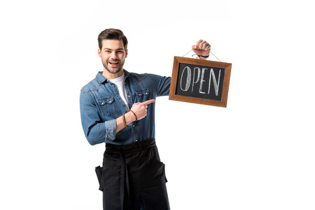 portrait of smiling waiter pointing at open blackboard in hand isolated on white Imagens