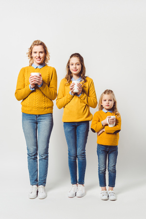 mother and daughters holding cups of hot hoffee on white