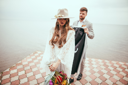 attractive bride in wedding dress and hat and groom on pier at lake