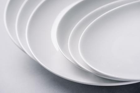 White ceramic plates stacked on white background Zdjęcie Seryjne