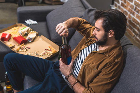 side view of loner opening bottle of alcohol drink at living room Stock Photo