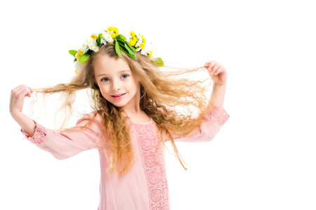 Smiling kid wearing wreath band from flowers and holding her hairs isolated on white Stockfoto