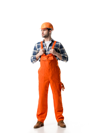 Confident handyman in orange overall and helmet isolated on white 写真素材 - 111570495