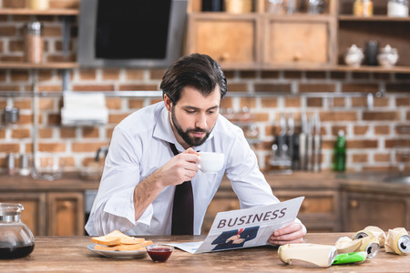 handsome loner businessman drinking coffee and reading newspaper in morning at kitchen