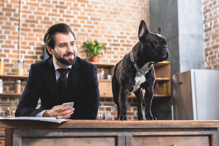 cheerful handsome loner businessman looking at dog at kitchen