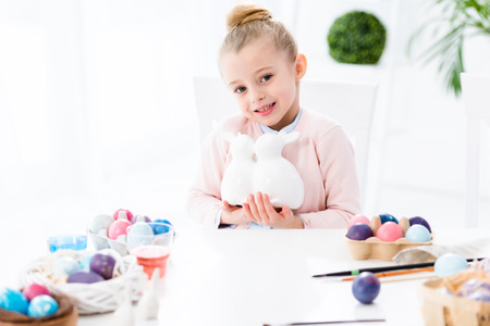 Kid girl holding bunny statuettes by Easter eggs