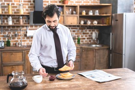 cheerful loner businessman adding jam on toast at kitchen