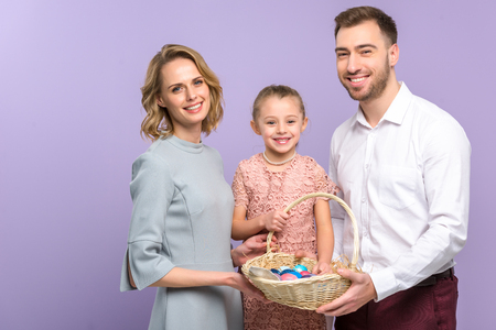 Parents and daughter with Easter basket with colored eggs isolated on violet Zdjęcie Seryjne