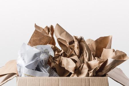 Vista de cerca de la caja de cartón con papeles en el interior aislado en blanco Foto de archivo