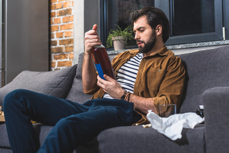 handsome loner looking at bottle of alcohol drink at living room