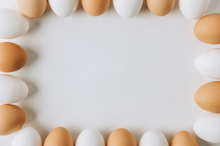 white and brown eggs laying on on white background and forming square