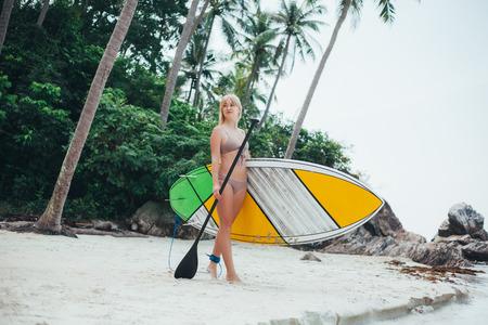 beautiful girl in bikini with paddle board on tropical beach