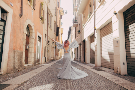 back view of elegant girl in glamorous dress on street of Verona