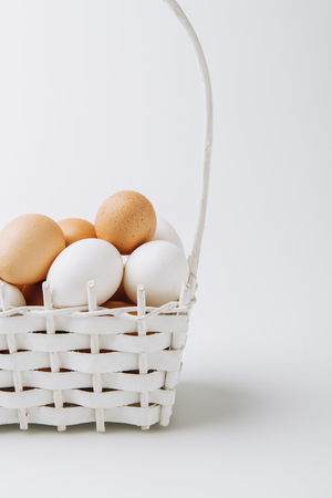 white and brown eggs laying in wicker basket on white background Stock fotó