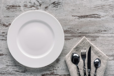 White plate and cutlery on napkin on wooden background