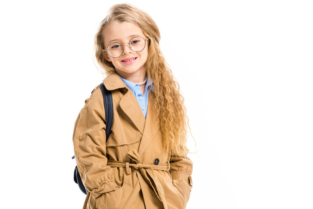 Little kid in glasses wearing trench coat and holding bag on shoulder isolated on white