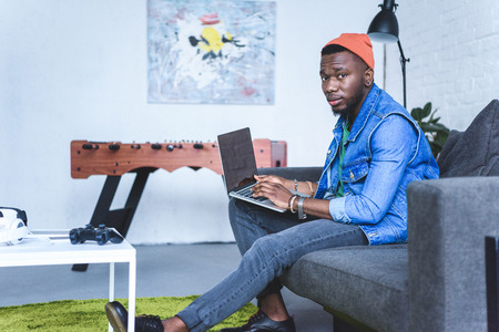 Handsome african american man working on laptop while sitting on sofa Reklamní fotografie