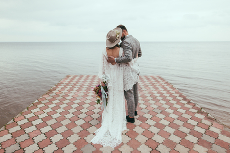 rear view of bride and groom in boho style hugging on pier at lake